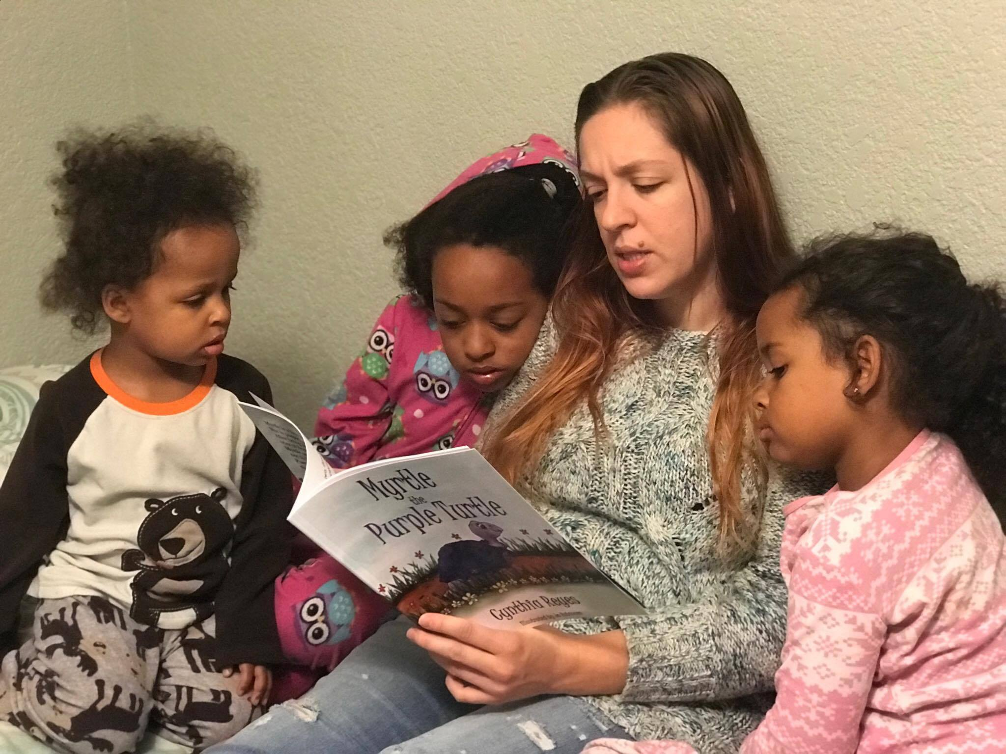 Blog Photo - Myrtle being read to children by Ashly