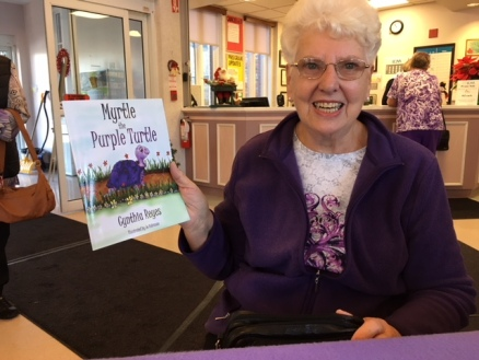 Blog Photo - BOAA - Lady holds Myrtle Book and smiles