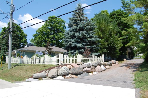 Blog Photo - Carol garden wide shot of fence and rocks and flowers from street